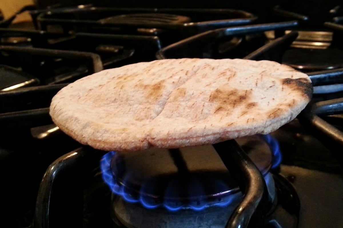 How to heat up Pita bread? Start by warming over a naked flame as described above. Once it puffs up with hot air, take off the flame and put it back into the plastic bag from whence it came.